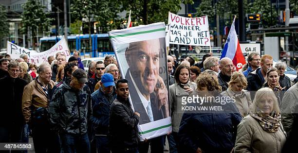 Protestors carry a photo of late farright Dutch politician Pim Fortuyn and a sign that reads 'Volkert when may you leave the country ' during a...