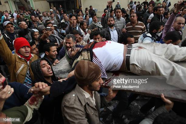 Protestors carry an injured man during clashes with riot police near Tahrir Square on January 29, 2011 in Cairo, Egypt. Tens of thousands of...