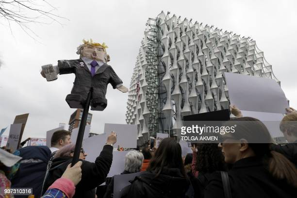 Protestors carry placards and shout slogans during a demonstration calling for greater gun control outside the US Embassy in south London on March 24...