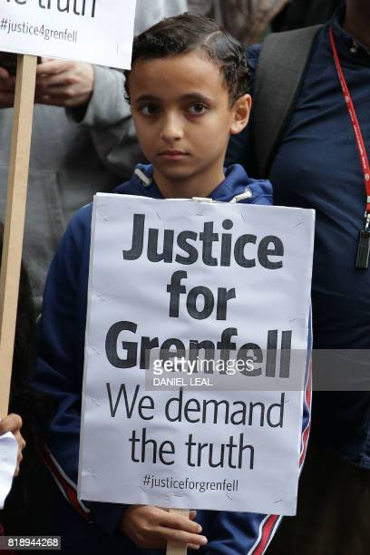 Protestors carry placards as they gather outside the Kensington Town Hall during a Kensington Council meeting to discuss Grenfell Tower the election...