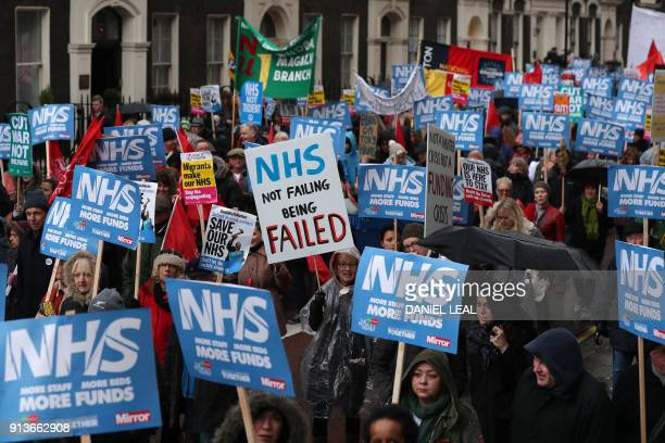 Protestors carry placards during a march calling for an end to the 'crisis' in the staterun National Health Service in central London on February 3...