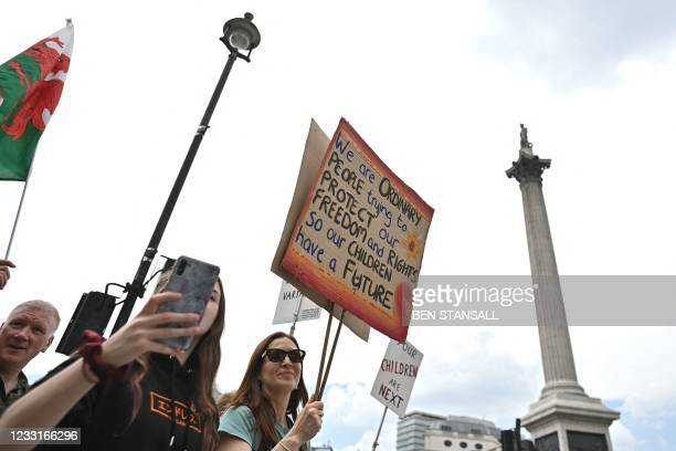Protestors carry placards during a 'Unite For Freedom' rally against Covid-19 vaccinations and government lockdown restrictions, in Trafalgar Square,...