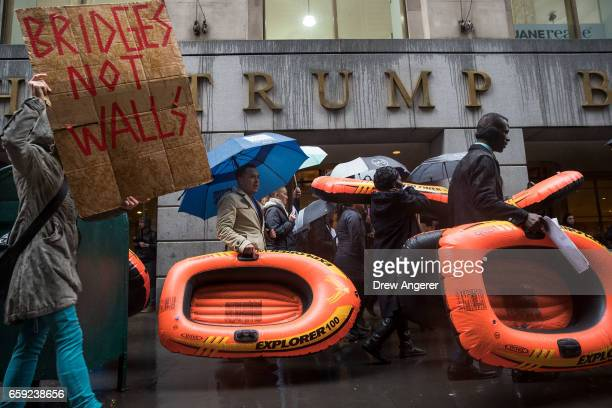 Protestors carry rafts signifying the struggle of refugees as they march past the Building on Wall Street during a protest against the Trump...