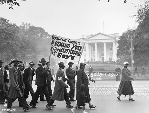 Protestors carry signs in front of the White House in 1933 demanding the freedom of imprisoned Scottsboro African American men accused of rape. The...