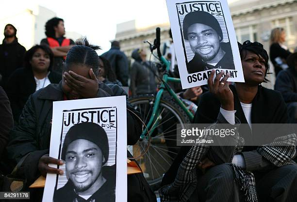 Protestors carry signs with a picture of slain 22yearold Oscar Grant III during a demonstration at Oakland City Hall January 14 2009 in Oakland...