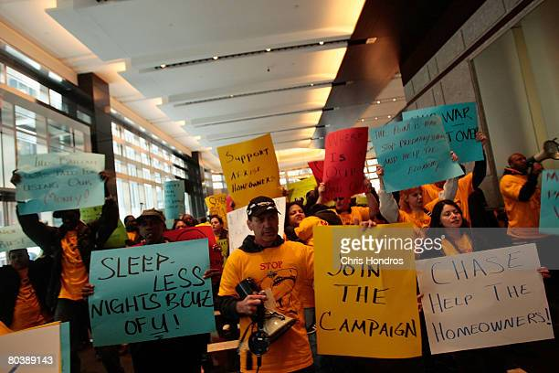 Protestors chant and carry signs in the lobby of the Bear Stearns headquarters March 26, 2008 in New York. Hundreds of housing activists overwhelmed...