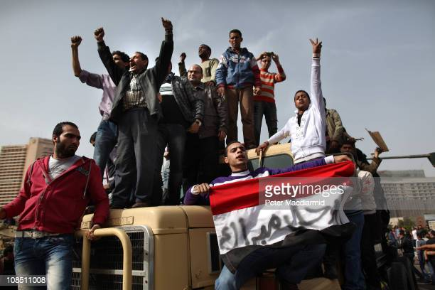 Protestors chant as they ride on an army tank transporter in Tahrir Square on January 29 2011 in Cairo Egypt Tens of thousands of demonstrators have...