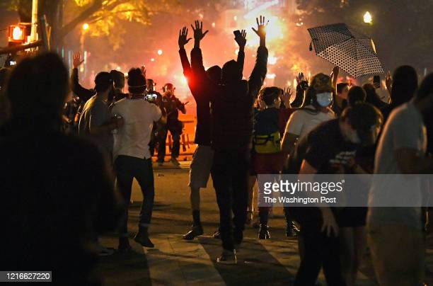 Protestors chant Hands up Don't Shoot as smoke from tear gas lingers in the air A large group of protestors lingered late at the perimeter of...