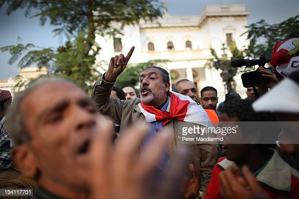 Protestors chant in front of the parliament building as they support a sitin at the nearby cabinet office on November 26 2011 in Cairo Egypt...