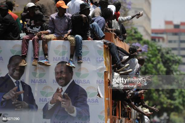 Protestors chant on the back of a campaign truck bearing the images of Kenya's opposition coalition National Super Allinace flag bearer and runnimg...