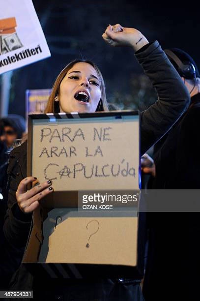 A protestors chants slogans and holds a shoebox with text reading 'We have no money ' as she marches to the entrance of a Halkbank bank branch in the...