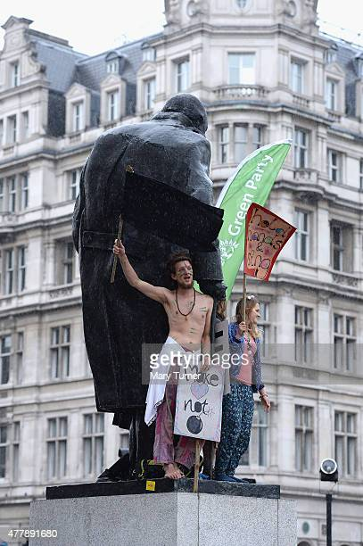 Protestors clamber over the statue of Winston Churchill in Parliament Square as demonstrators below gather to protest against austerity and spending...
