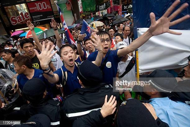 Protestors clash with police as they try to cross a road to join a rally in Hong Kong China on Monday July 1 2013 Thousands of people began a rally...