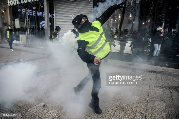 TOPSHOT Protestors clash with riot police amid tear gas during a demonstration of Yellow vests on the Champs Elysees in Paris on November 24 2018...