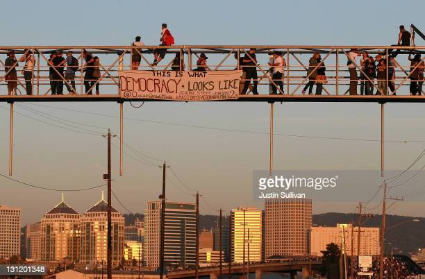 Protestors climb on a railroad crossing at the Port of Oakland during Occupy Oakland's general strike on November 2 2011 in Oakland California Tens...