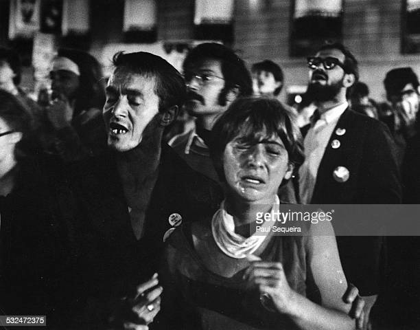 Protestors close their eyes in pain as they react to tear gas having been fired by police officers during the Democratic National Convention Chicago...