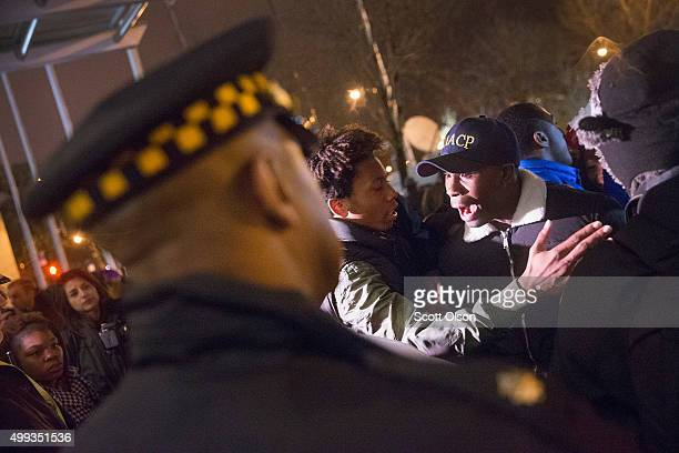 Protestors confront police guarding the fromt of Chicago police headquarters during a prayer vigil and demonstration called to protest the death and...