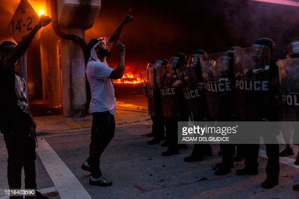 Protestors confronts riot police in front of a burning police car during a protest against police brutality in Miami Florida on May 30 2020 in...