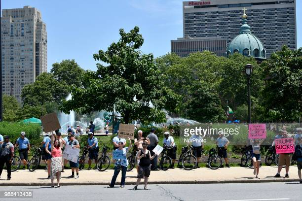 Protestors counter a Trump supporter looking on from the side as thousands participate in a rally to protest the Trump's administration immigration...