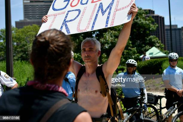 Protestors counter Howard Caplan a local Trump supporter who holds a sign that reads God Bless Trump as he stands surrounded by Police officers...