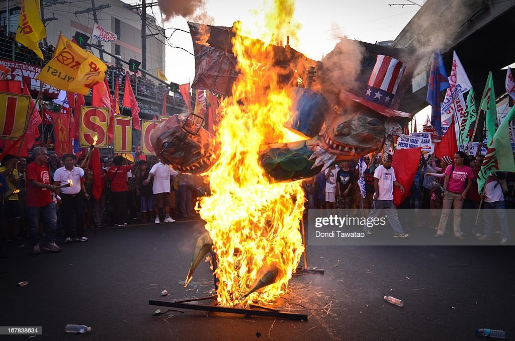 Protestors cricle around a burning effigy of Philippine president Benigno Aquino and US president Barack Obama on May 1, 2013 in Manila, Philippines. Philippine workers unions gather in the streets of Manila to demand, among other things, better pay, an end to contractualization and layoff and the lowering of prices of basic commodities. Labor day is celebrated across South East Asia on May 1st and is seen as an opportunity to acknowledge the social and economic accomplishments of the workers.
