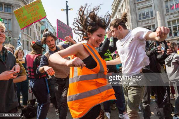 Protestors dance during a performance by Electro duo The Correspondents during a protest against climate change in the middle of Oxford Circus on...