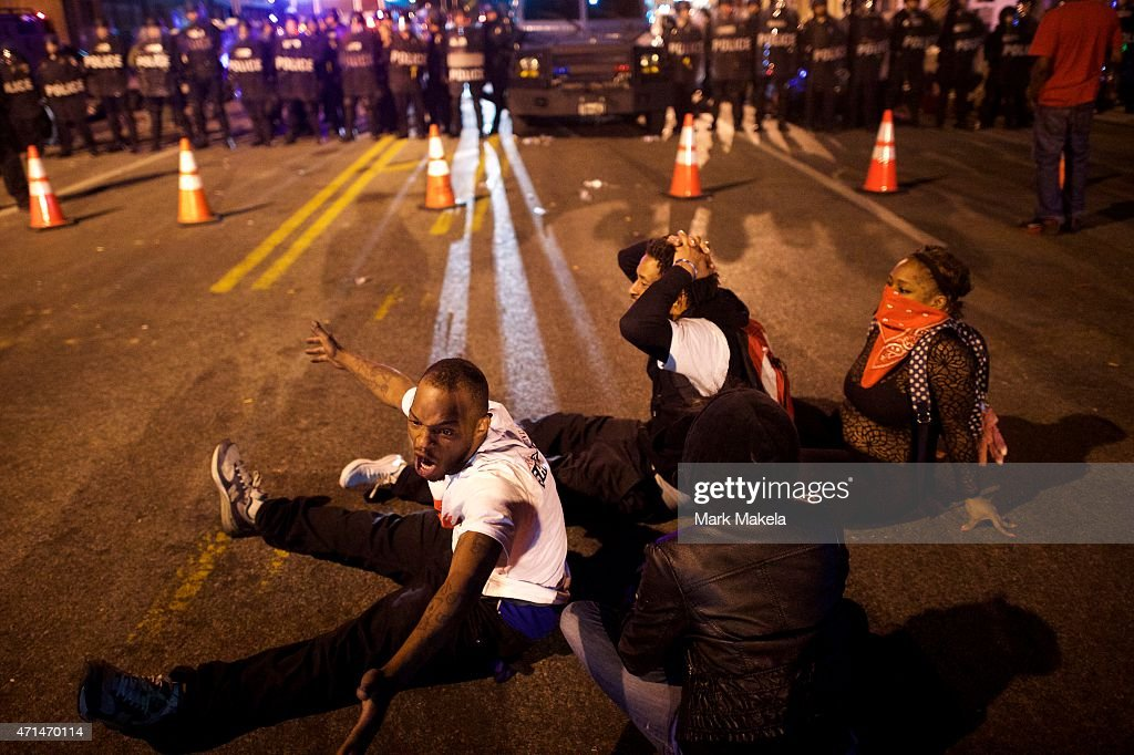 Protestors defy curfew in front of police officers the night after citywide riots over the death of Freddie Gray on April 28, 2015 in Baltimore, Maryland. Freddie Gray, 25, was arrested for possessing a switch blade knife April 12 outside the Gilmor Houses housing project on Baltimore's west side. According to his attorney, Gray died a week later in the hospital from a severe spinal cord injury he received while in police custody.