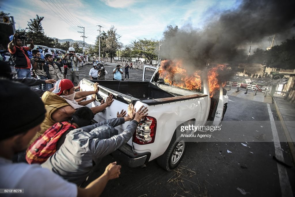 Protestors demanding justice and clarification of the disappearance of 43 students from Ayotzinapa stage clash with police in front of the 27th infantry battalion headquarters in Iguala, Mexico on January 13, 2015. Trucks are damaged and set on fire during protest.
