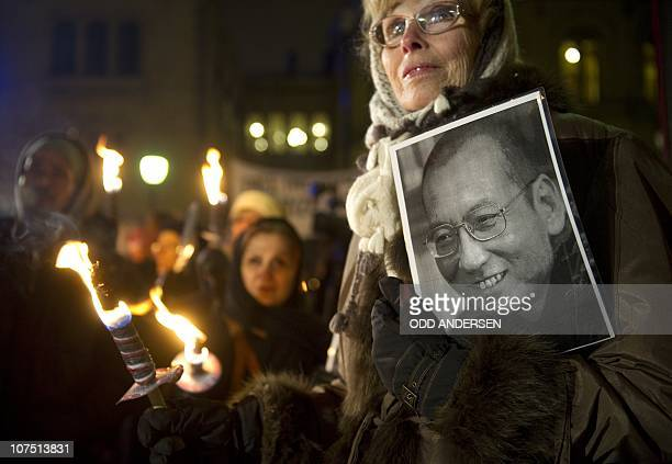 Protestors demanding the release of the Nobel Laureate and dissident Liu Xiaobo holds his portrait during a torch parade in his honour in Oslo on...