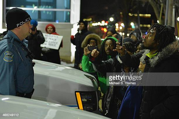 Protestors demonstrate and film a police officer outside the Ferguson Police Department in Ferguson Missouri on March 4 2015 The Federal Department...