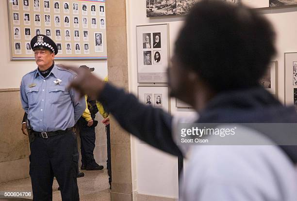 Protestors demonstrate outside the city council chambers y as Chicago Mayor Rahm Emanuel addresses a special session of the City Council as his...