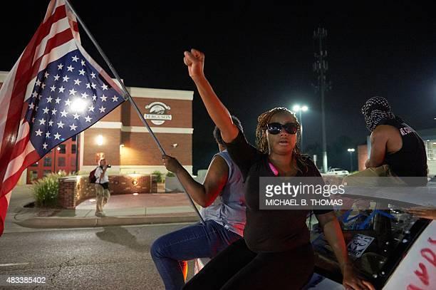 Protestors demonstrate outside the Ferguson Police Department in Ferguson Missouri on August 7 2014 As the embattled community celebrates the one...