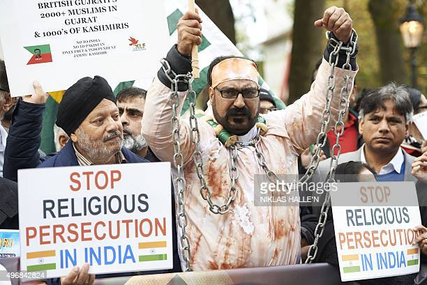 Protestors demonstrating against Indian Prime Minister Narendra Modi hold placards by Parliament square in central London on November 12 2015 India's...