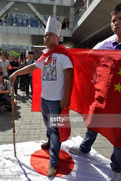 Protestors display banners and pictures of Chairman Mao while chanting slogans during their march towards the Japanese Consulate in Shanghai China on...