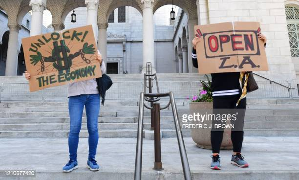 Protestors display placards on the steps of City Hall demanding the Stay at Home order to be lifted and the government to reopen the state during an...