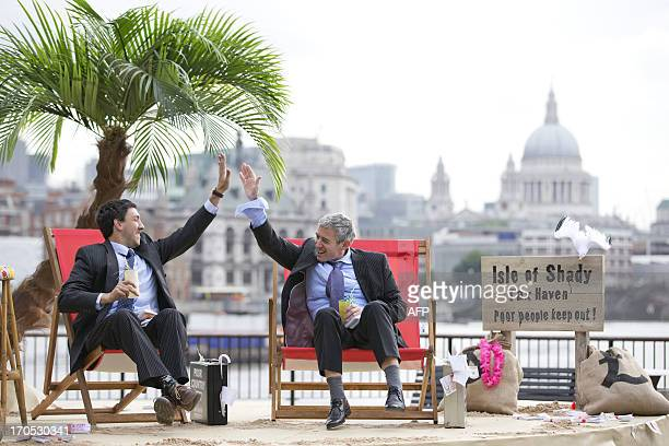 Protestors dressed as a businessman do a 'high five' on a protest site named by participants as the 'Isle of Shady Tax Haven' in London on June 14...
