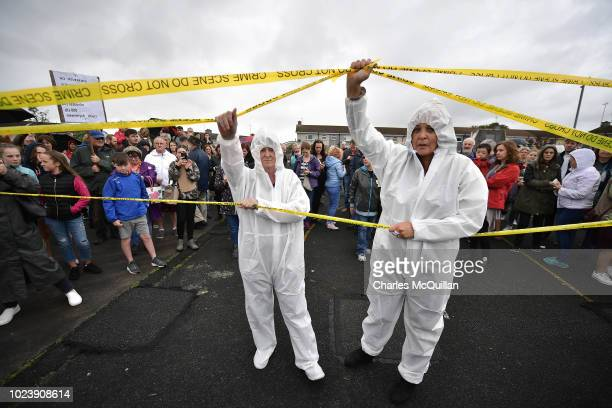 Protestors dressed as crime scene officers take part in a demonstration protest as a vigil takes place at the site of the mass grave which contained...