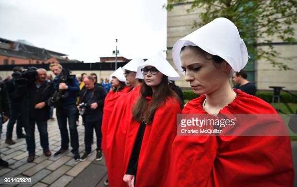 Protestors dressed as hand maidens stand as abortion rights campaign group ROSA Reproductive Rights Against Oppression Sexism and Austerity...