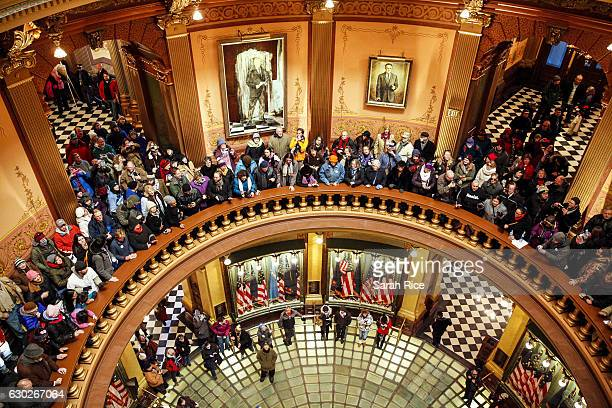Protestors fill the rotunda of the Michigan State Capitol before the state electoral college met to cast their votes on December 19 2016 in Lansing...