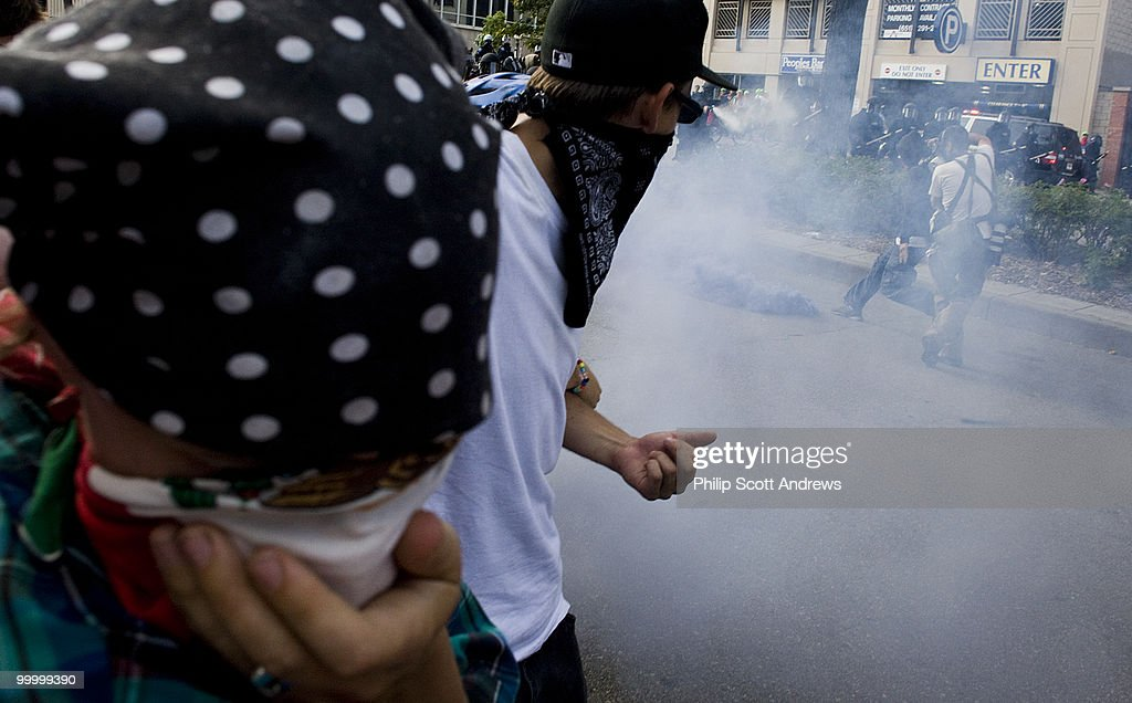 Protestors flee from tear gas fired by riot police. The police used a combination of tear gas, mace and clubs to maintain order and control of the protest.