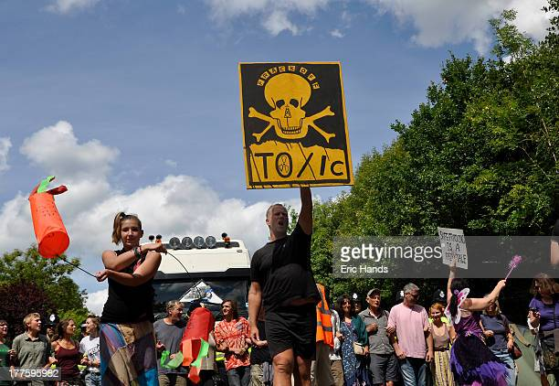 Protestors form a chain and attempt to prevent delivery lorries from entering a Cuadrilla drilling site at Balcombe, one holding a placard with the...
