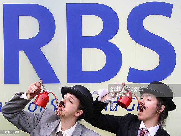 Protestors from the UK Tar Sands Network drink from oil cans as they demonstrate against the RBS backing the controversial extraction of oil from tar...