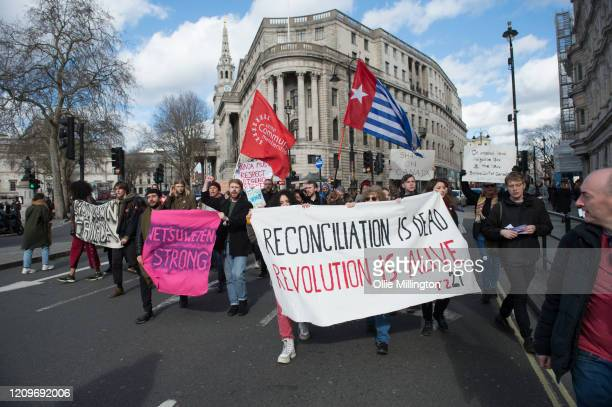 Protestors from twelve British climate emergency conscious groups hold a solidarity march To Downing Street from The High Commission of Canada at...