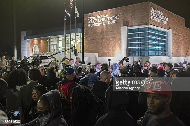 Protestors gather and shout slogans in front of the Ferguson Police Department during ongoing protests after the Justice Department released their...