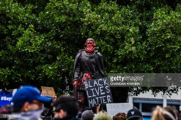 Protestors gather around a vandalised statue of Former Governor of Puerto Rico, Juan Ponce de Leon in Downtown Miami on June 12, 2020 in Miami,...