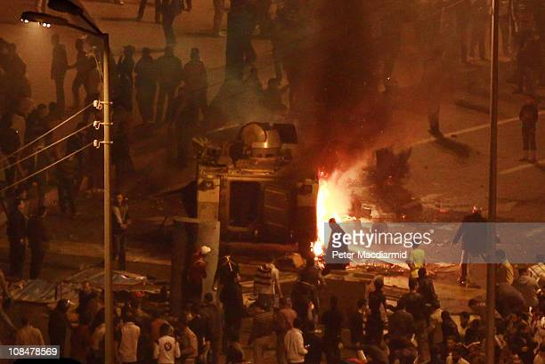 Protestors gather round a burning armoured personnel carrier in Tahrir Square on January 28 2011 in Cairo EgyptThousands of police are on the streets...