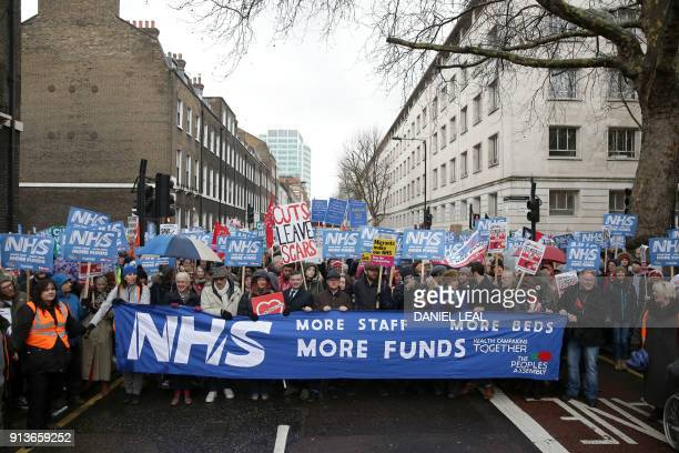 Protestors gather with placards amd banners at the start of a march calling for an end to the 'crisis' in the staterun National Health Service in...