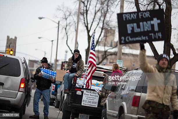 Protestors hand out water to Flint residents during a rally on January 24 2016 at Flint City Hall in Flint Michigan The event was organized by...
