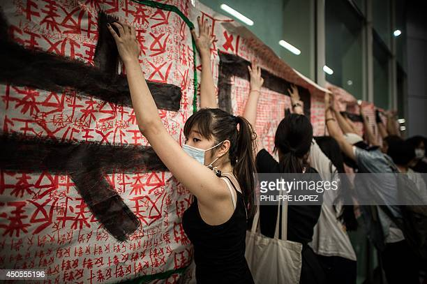 Protestors hang a banner on a door of the Legislative Council in Hong Kong on June 13 2014 Riot police were deployed to prevent protestors gaining...