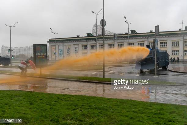 Protestors hide beneath an umbrella as police forces use water cannons to disperse the crowds during the 10th Sunday March on October on October 11,...